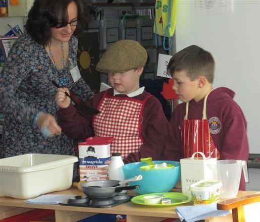 Children from Pontybrenin School, Gorseinon, dressed as Da-cu and Emyr Rhys making Welsh cakes