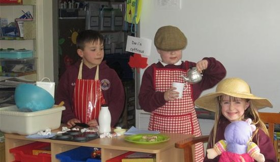 Children from Pontybrenin School, Gorseinon, dressed as Emyr Rhys and Da-cu offering Nain a cup of tea and a Welsh cake