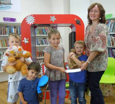 Aimee Edwards, winner of Llanelli Library's Mythical Maze treasure hunt, receiving her prize from author Wendy White.